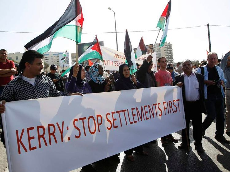 Palestinian protesters hold flags and a banner during a demonstration against U.S. Secretary of State John Kerry's visit, in the West Bank town of Bethlehem