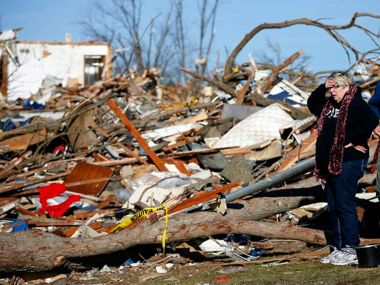 Woman looks at what is left of her home after it was destroyed during a tornado in Washington