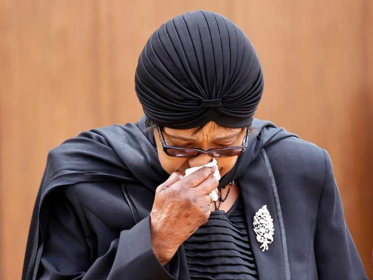 Winnie Mandela, ex-wife of former South African President Nelson Mandela, looks down while viewing his coffin as he lies in state at the Union Buildings in Pretoria