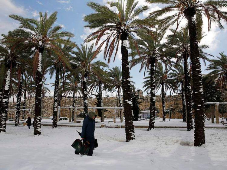 A man walks through snow near Jerusalem's Old City walls