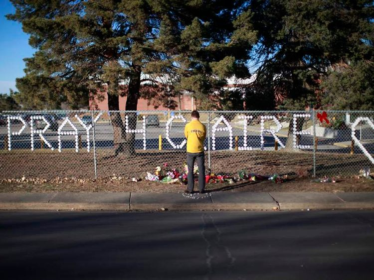 An Arapahoe high school student prays at the school in Centennial, Colorado
