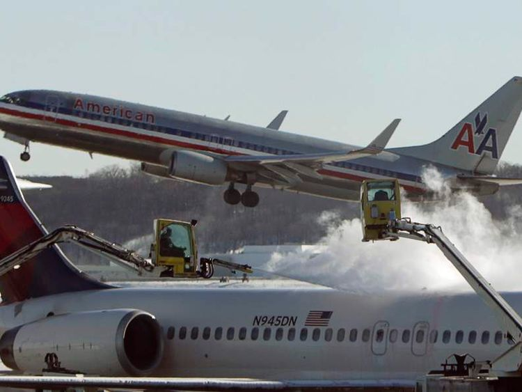 A Delta jetliner is de-iced while an American Airlines plane takes off at Reagan National Airport in Washington