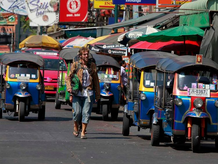 A tourist walks alongside auto rickshaw taxi cabs at Khao San Road tourist district in the morning after a shooting incident at an intersection near the street