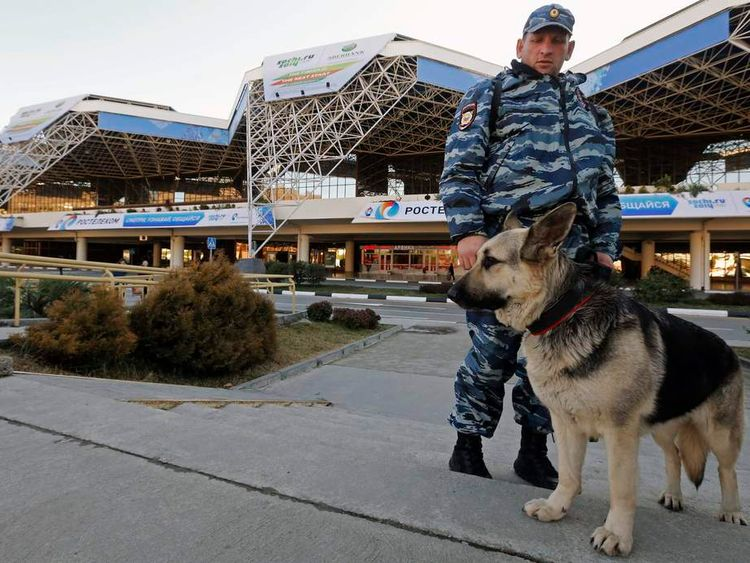 Russian policeman Vladislav and Lora, a german shepherd sniffer dog, stand guard in front Sochi's airport
