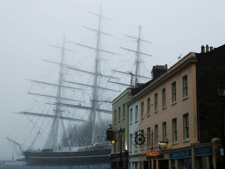 The Cutty Sark is pictured behind buildings at Greenwich in London