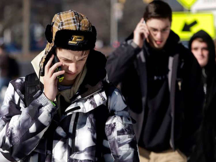Students talk on their mobile phones after a campus lockdown was lifted at Purdue University in West Lafayette