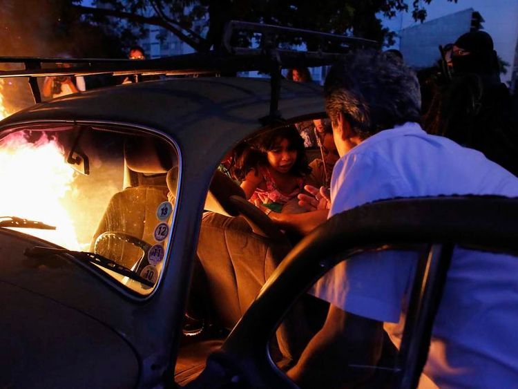 A man helps his family out of their car, which caught fire after driving through a flaming barrier during a protest against the 2014 World Cup in Sao Paulo