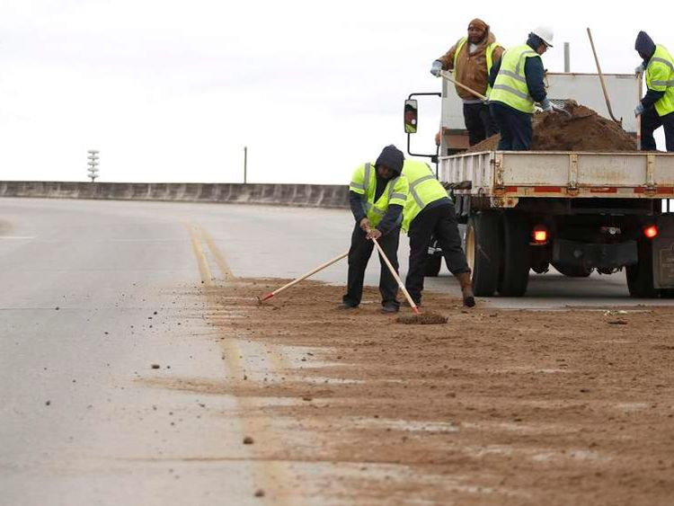 Workers with the city of Mobile shovel dirt on a bridge as cold weather descends on Mobile, Alabama