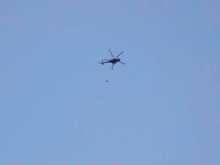 A helicopter loyal to Syrian President Bashar Al-Assad throws what activists say is an explosive barrel, in Al-Shaar area in Aleppo