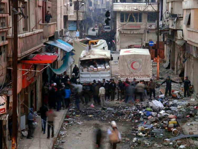 Syrian Arab Red Crescent trucks stand in the besieged neighbourhoods of Homs to supply humanitarian aid