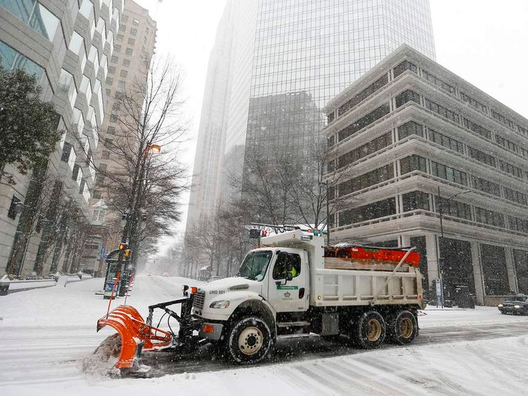 A Charlotte city plow works to clear a street in Charlotte