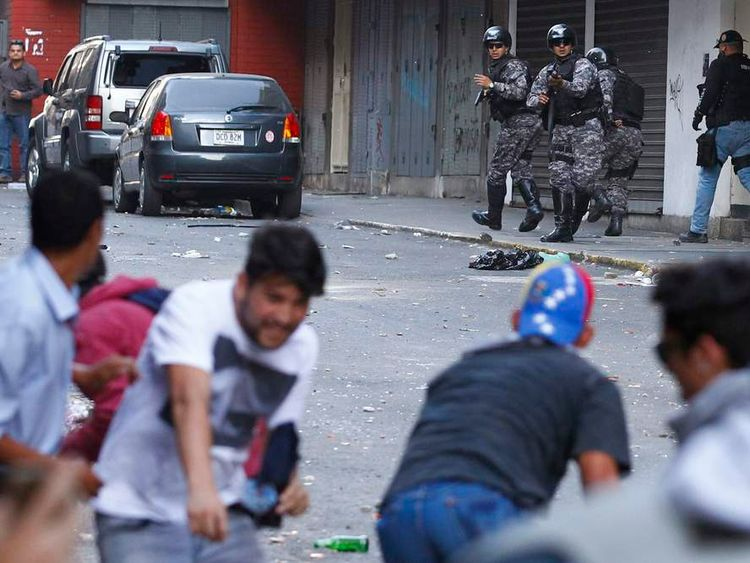 Police officers clash with opposition demonstrators during a protest against Venezuela's President Maduro's government in Caracas