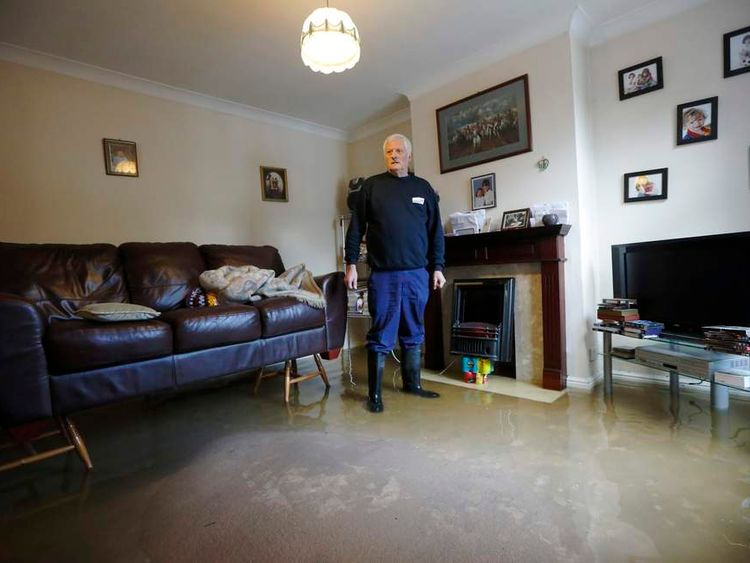 Michael Simmonds stands in the flooded living room at his Egham home