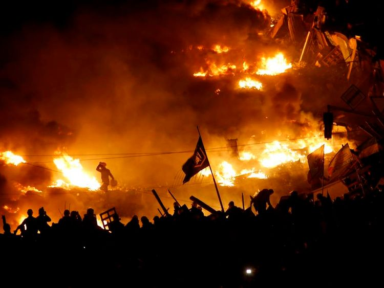 Anti-government protesters stand behind burning barricades in Kiev's Independence Square.