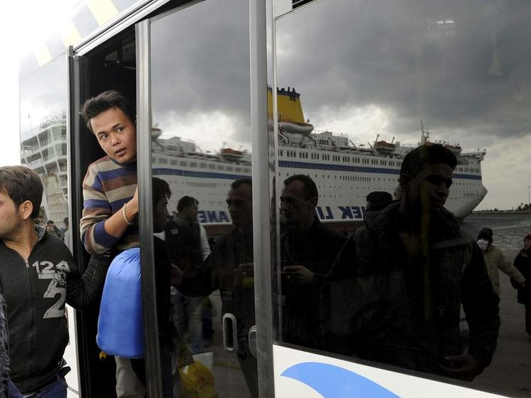 Refugees and migrants board a bus after arriving aboard the passenger ferry Eleftherios Venizelos from the island of Lesbos at the port of Piraeus, near Athens