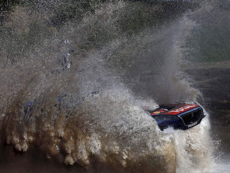 Loeb of France drives his Peugeot through the water during the Buenos Aires-Rosario prologue stage of Dakar Rally 2016 in Arrecifes