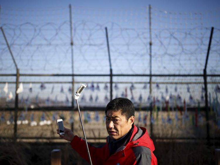 A tourist takes a selfie in front of a barbed wire fence near the demilitarized zone separating the two Koreas in Paju