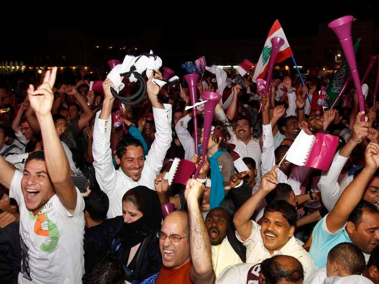 People celebrate after Fifa announce that Qatar will be host of the 2022 World Cup in Souq Wakif in Doha