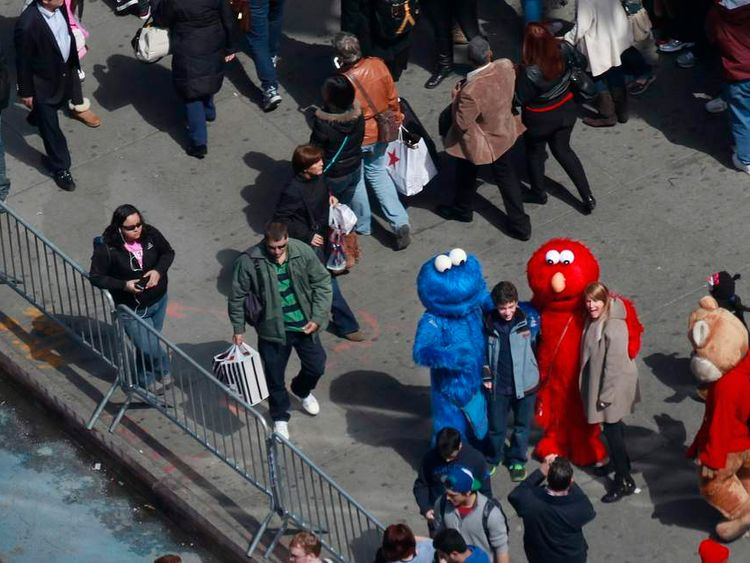 People pose for photos with characters dressed up as Elmo and Cookie Monster in Times Square in New York