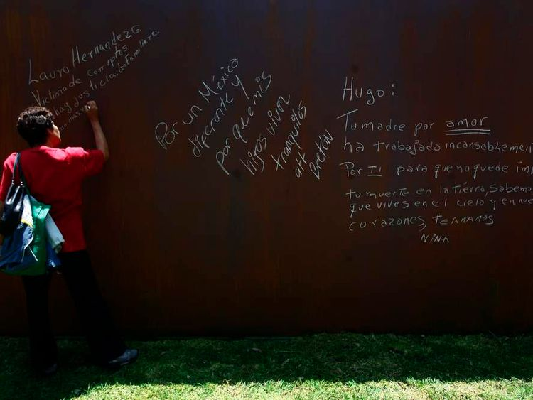 "A woman writes the name of a relative killed on a steel panel during the inauguration of ""Memorial to Victims of Violence in Mexico"" monument in Mexico City"