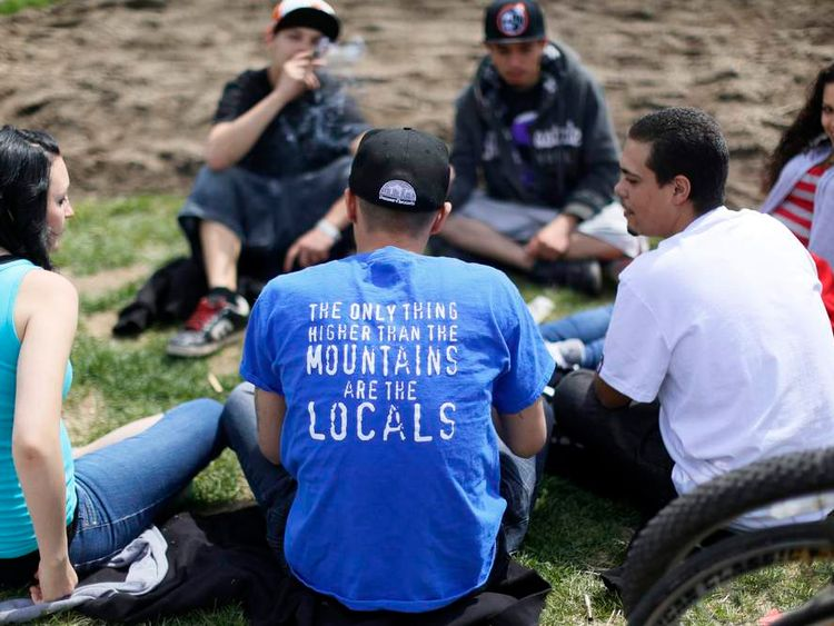 A man wearing a t-shirt referring to Colorado legalizing marijuana smokes at the 4/20 marijuana holiday in Civic Center Park in downtown Denver