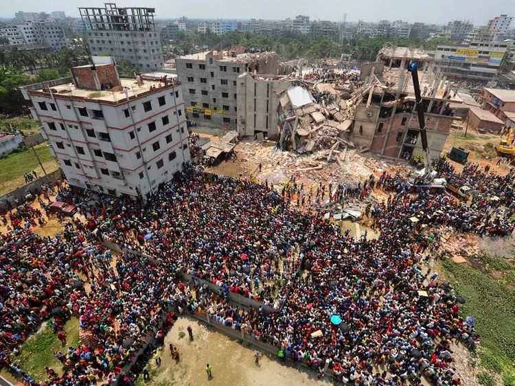 People gather in front of Rana Plaza building as rescue workers continue their operations, in Savar, 30 km (19 miles) outside Dhaka.