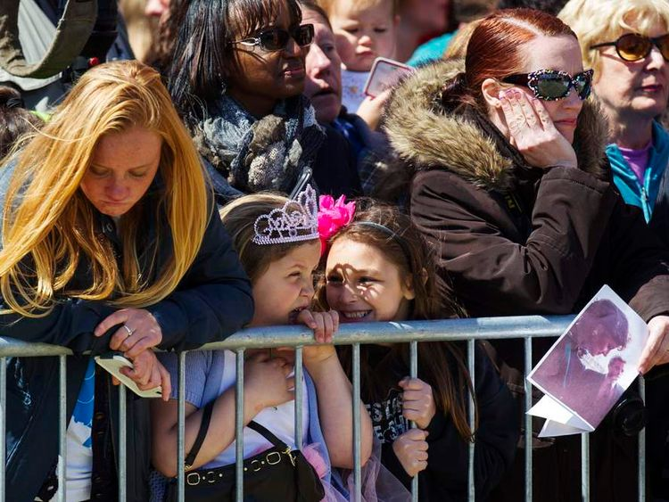 Girls await the arrival of Britain's Prince Harry, who will view areas of the boardwalk that have been repaired in Seaside Heights after Hurricane Sandy, in New Jersey