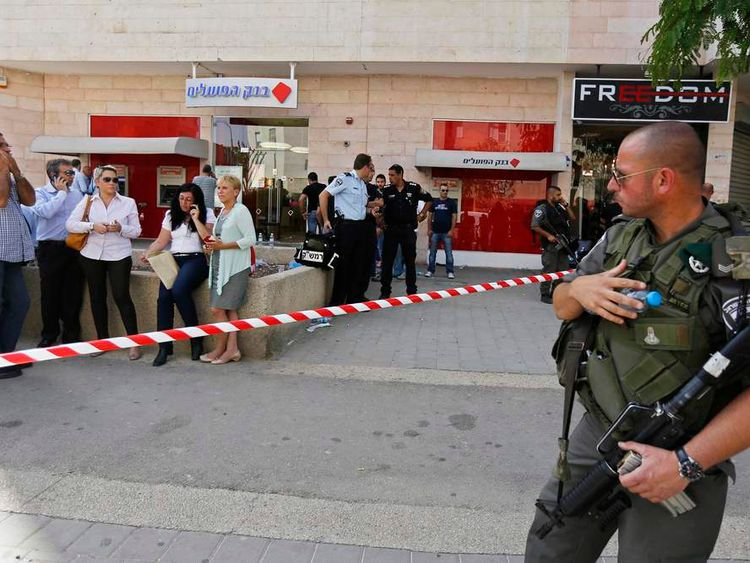 An Israeli policeman stands guard at the scene of a shooting at a Bank Hapoalim branch in Beersheba
