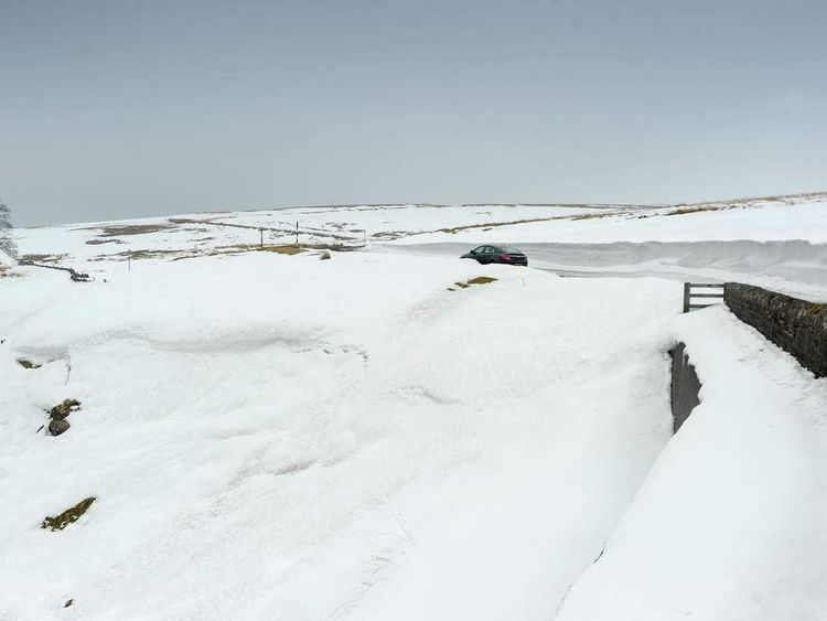 A car travels through the snow near Allenheads in Northumberland as temperatures remain around freezing.