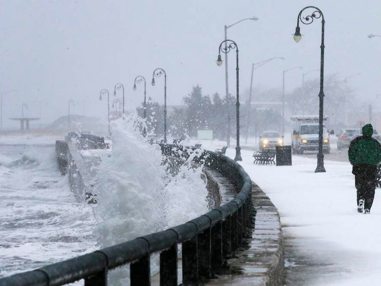 A man jogs past waves crashing against the seawall around high tide during a winter nor'easter snowstorm in Lynn