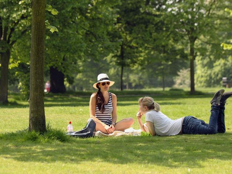 Two women relax in sunshine in Hyde Park, London