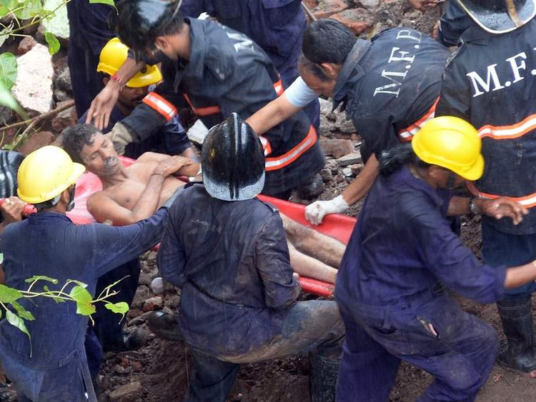 Firefighters and rescue workers bring out a survivor from under the rubble of a collapsed building in Mumbai