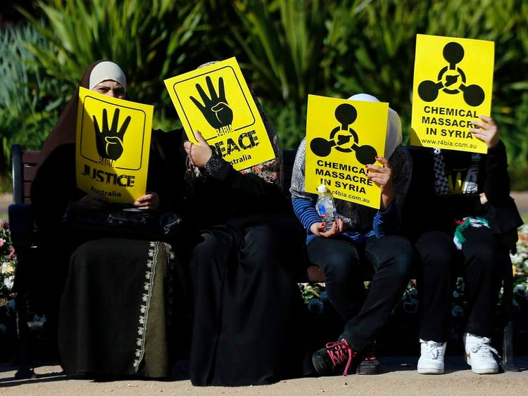 Muslim women hold placards against the Syrian government during a rally against the governments of Syria and Egypt in central Sydney