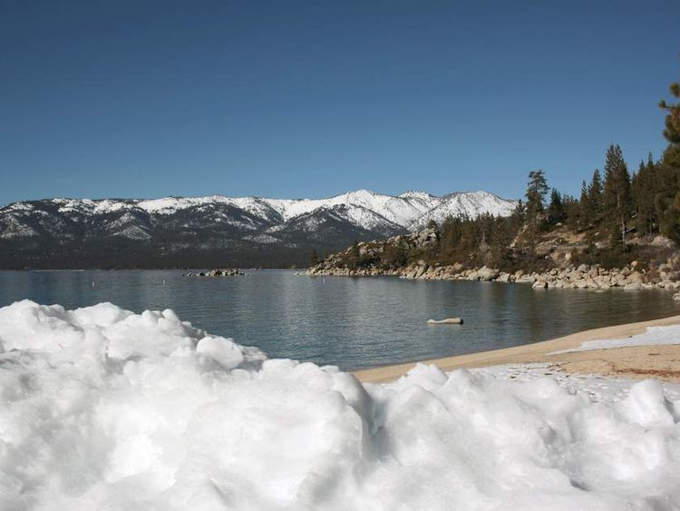 Snow is piled on a Lake Tahoe beach in Sand Harbor, Nevada