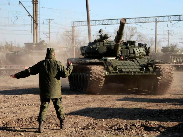 A Russian serviceman directs Russian tanks after their arrival in Crimea in the settlement of Gvardeiskoye near the Crimean city of Simferopol