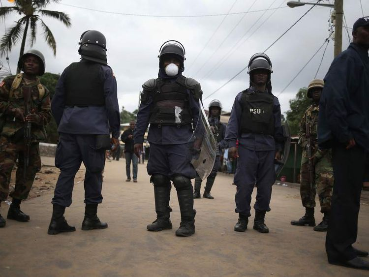Members of Liberia's Ebola Task Force enforce a quarantine on the West Point slum
