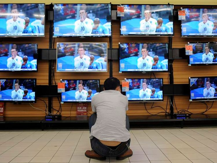 A man crouches in front of television sets broadcasting recorded footage of 2014 Brazil World Cup group match between England and Uruguay, at a home appliances store in Wuhan