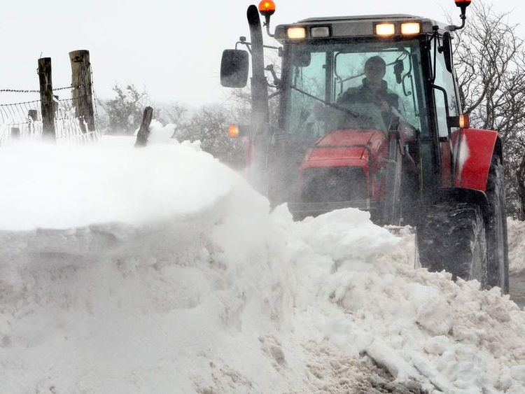 A tractor attempts to clear drifting snow in the hills above the Glens of Antrim, Northern Ireland.