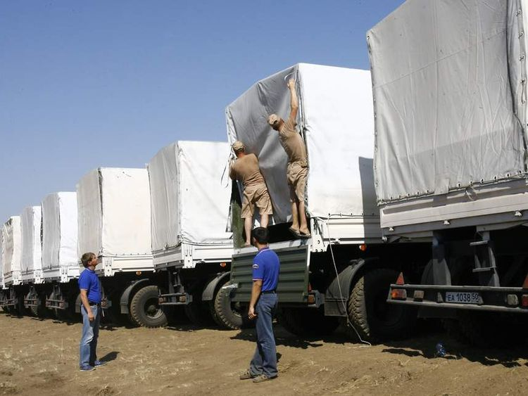 Russian truck drivers checks on their cargo of humanitarian aid
