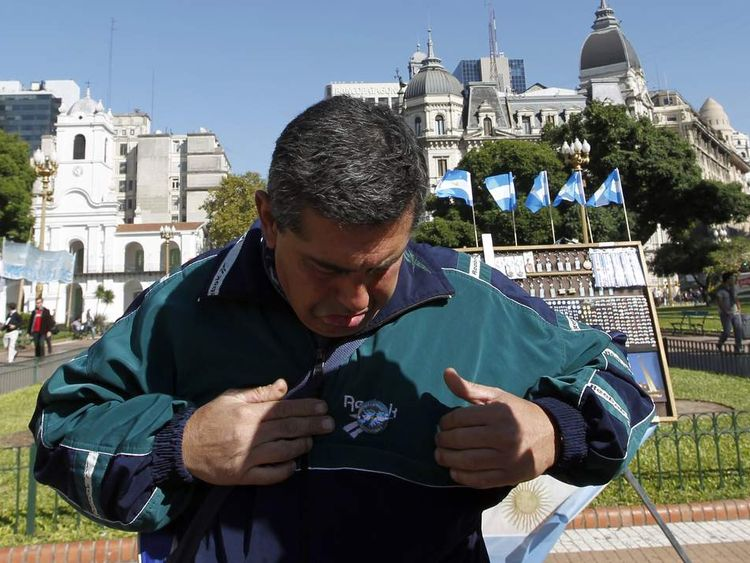 Argentine Walter Nunez, who took part in the 1982 South Atlantic conflict between Britain and Argentina, puts on a pin representing the Falkland Islands