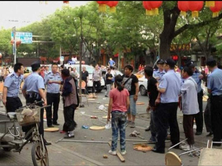 Police attempt to intervene in a fight between Tibetans and Han Chinese