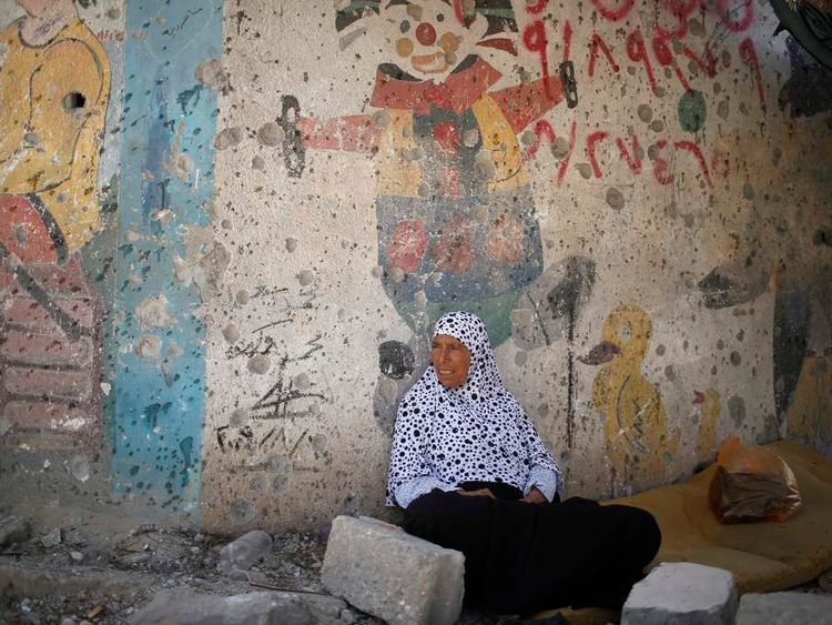 A Palestinian woman returns to her destroyed house during a 72-hour truce in Beit Hanoun town in the northern Gaza Strip