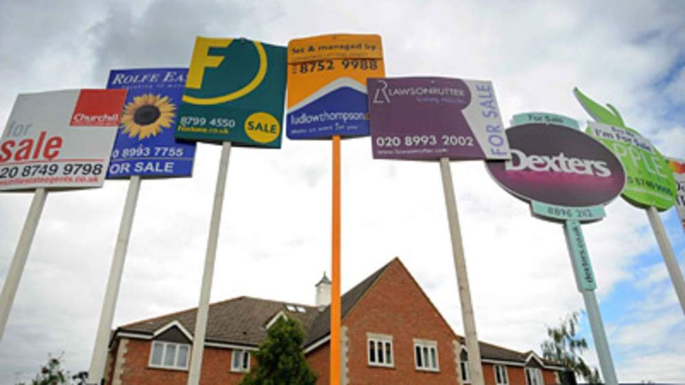 House for sale signs against cloudy sky