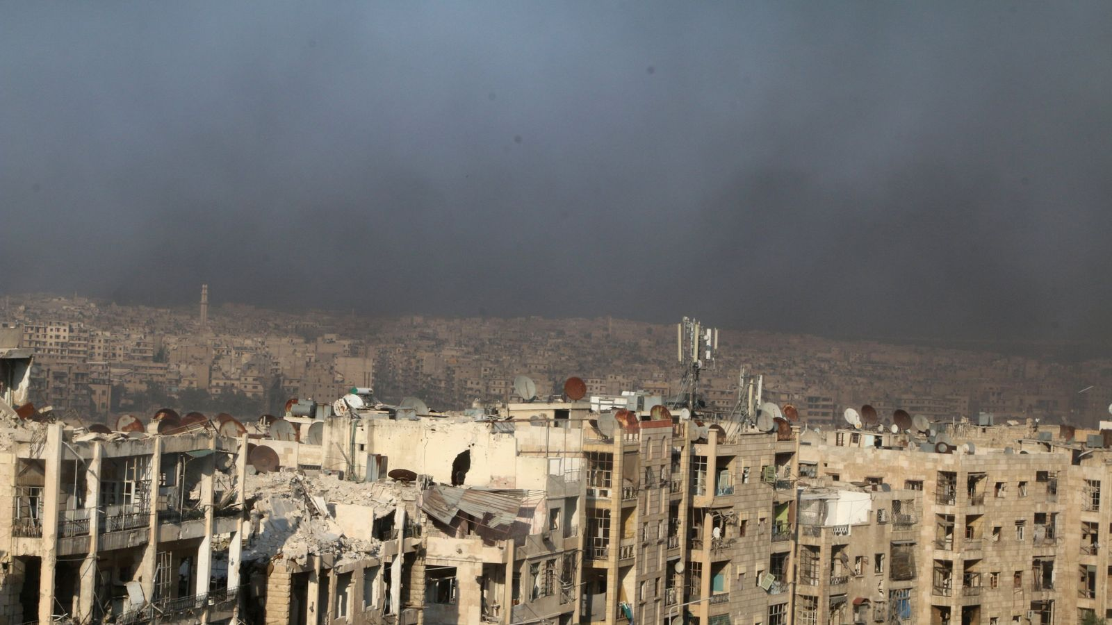 A general view shows rising smoke from burning tyres, which activists said are used to create smoke cover from warplanes, in Aleppo