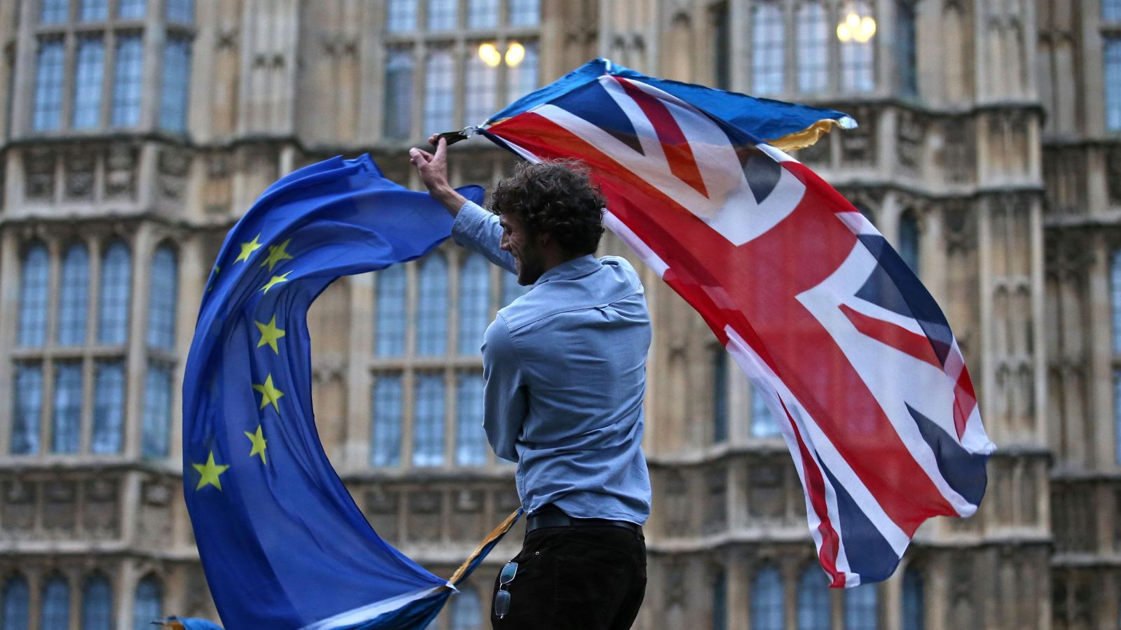 A man waves both a Union flag and a European flag together on College Green outside The Houses of Parliament at an anti-Brexit protest in central London