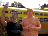 A passerby takes a selfie with a statue depicting republican presidential nominee Donald Trump in San Francisco