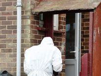 A forensic officer outside the property
