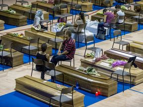 Relatives sit by coffins ahead of a state funeral on Saturday