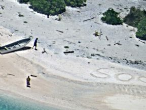 Two people shipwrecked on Chuuk State island in the Pacific draw SOS in the sand