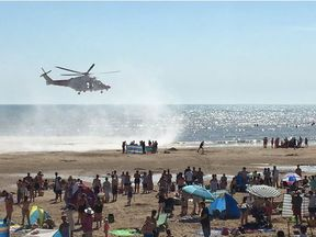 A helicopter hovers over rescuers after the men are pulled from the sea